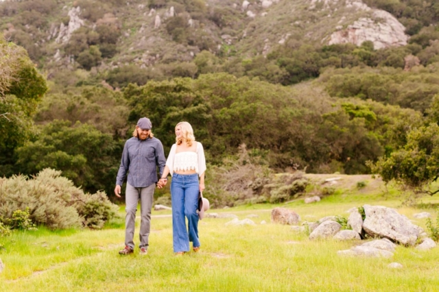 Couple strolling in the green hills of San Luis Obispo at their engagement session