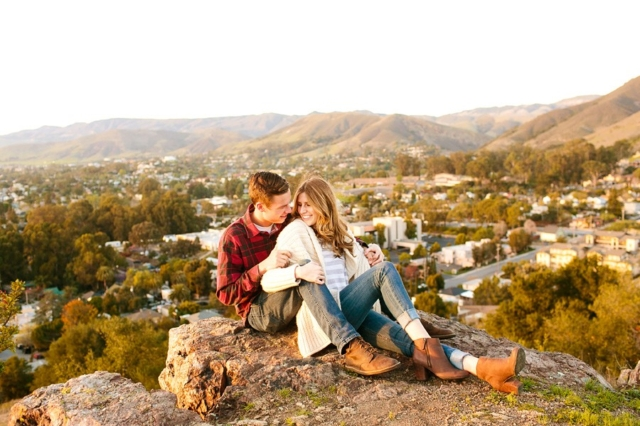 Stylish couple laughing together above San Luis Obispo in their engagement photos