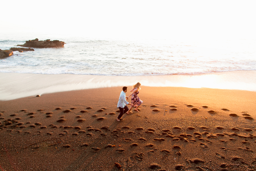 Fun couple running together on the beach in San Luis Obispo engagement photos