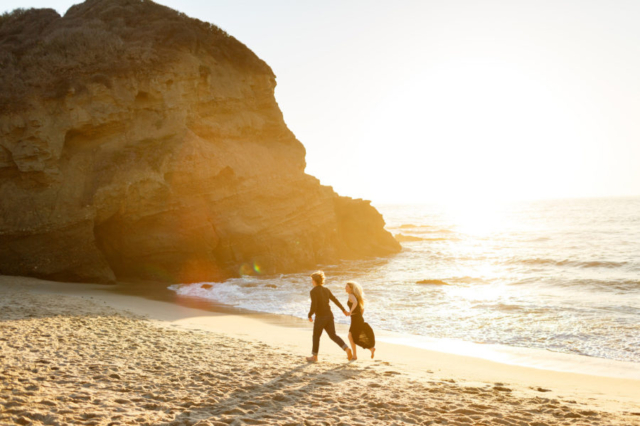 Laguna Beach couple running at sunset during engagement session