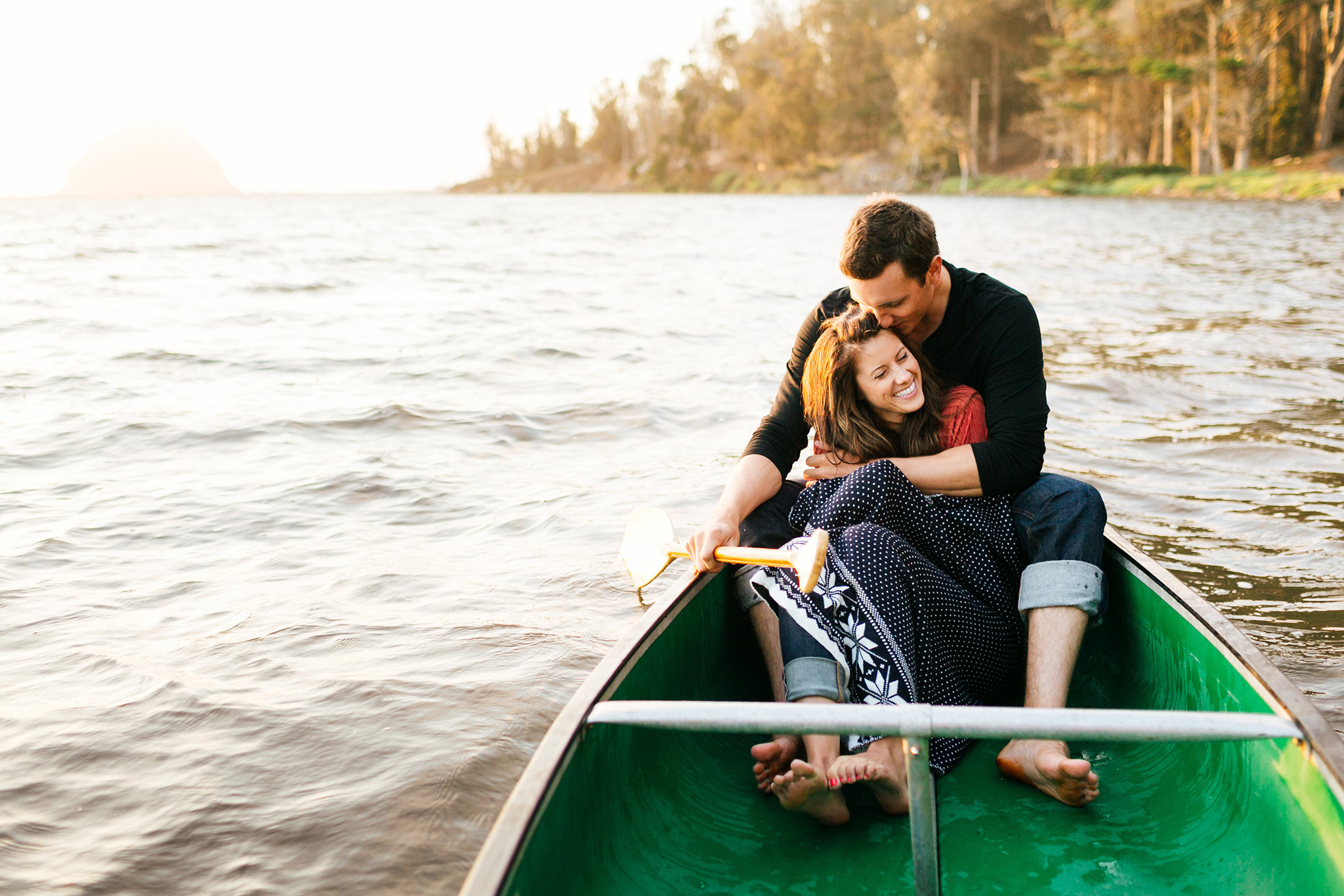 Cute couple cuddling in a canoe in Morro Bay engagement session
