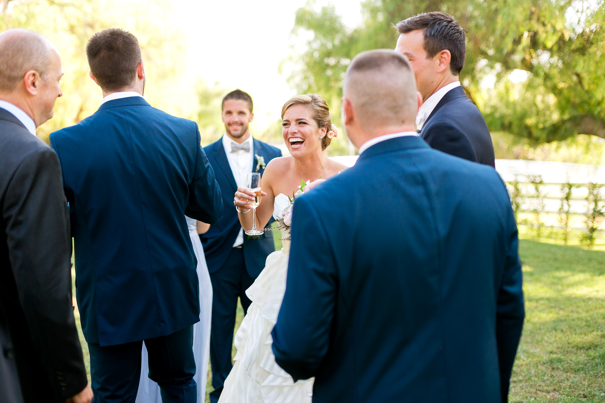 Candid photo of bride laughing with her wedding party
