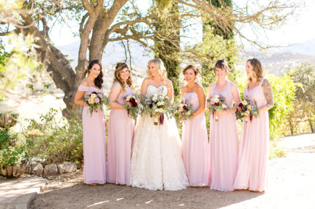 Bride and bridesmaids laughing together with bouquets and pink dresses in Paso Robles