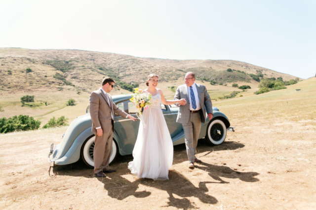 Father of the bride helping his daughter out of a classic car to walk her down the aisle