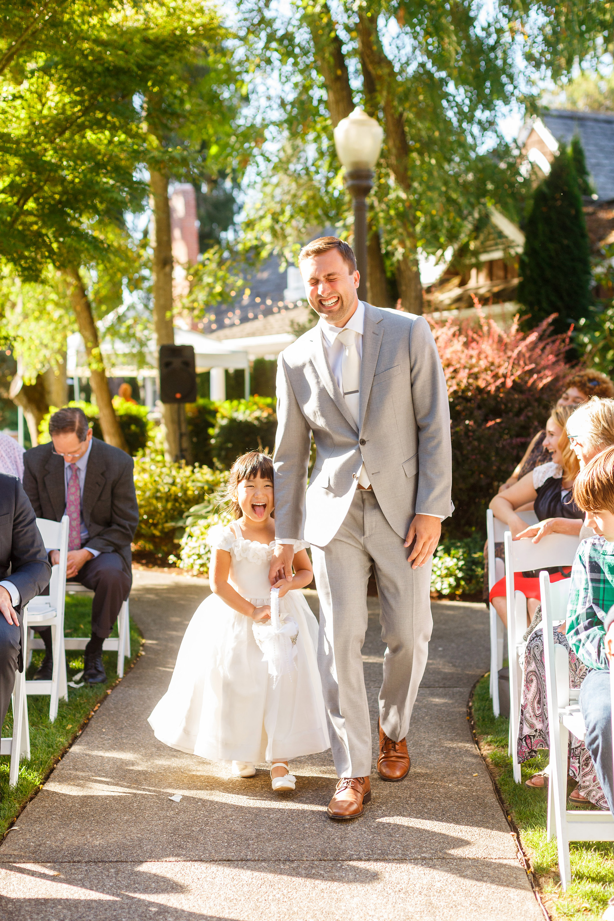 Groom walks flower girl down the aisle, laughing the whole way
