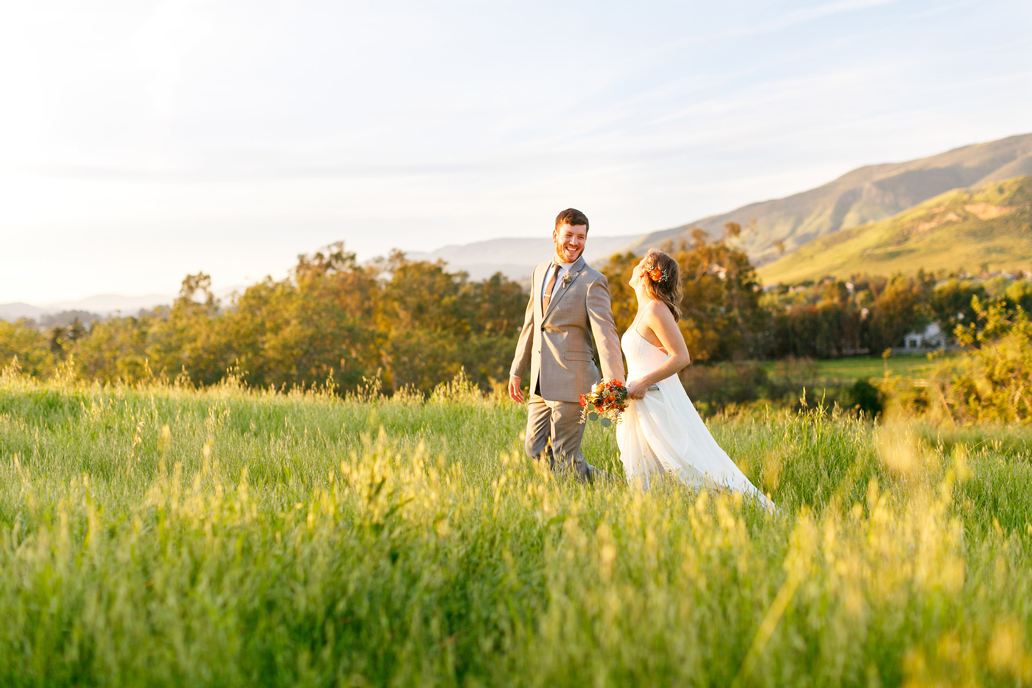 Groom leads his bride into the fields at Flying Caballos Ranch in San Luis Obispo