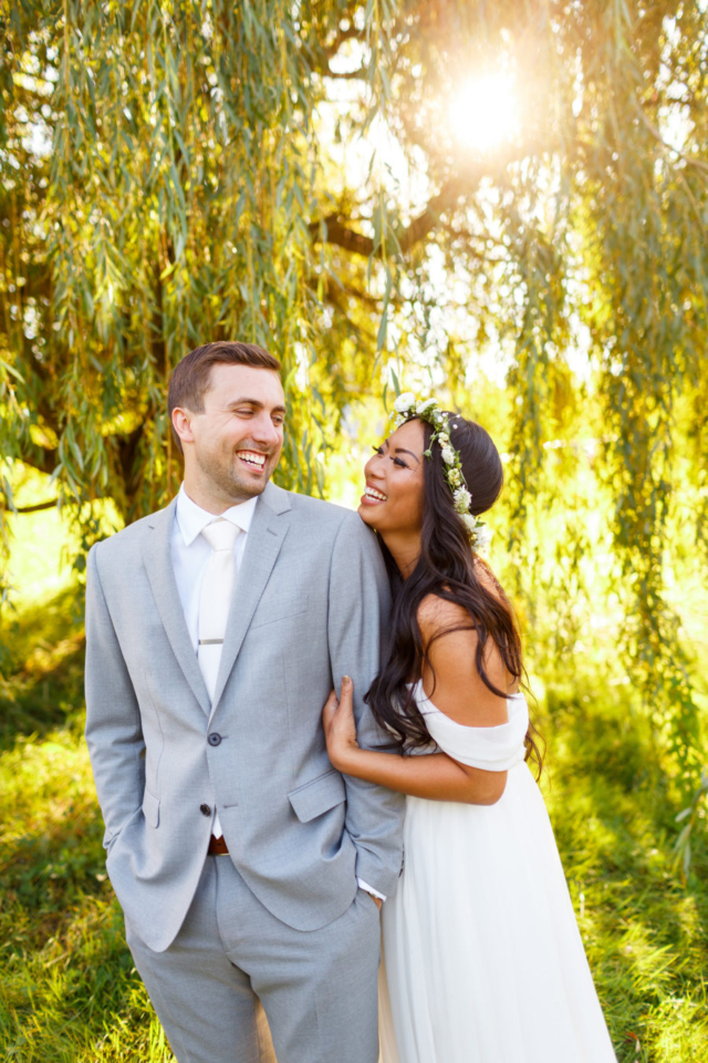Bride and groom laughing together under a willow tree. San Luis Obispo wedding photographers