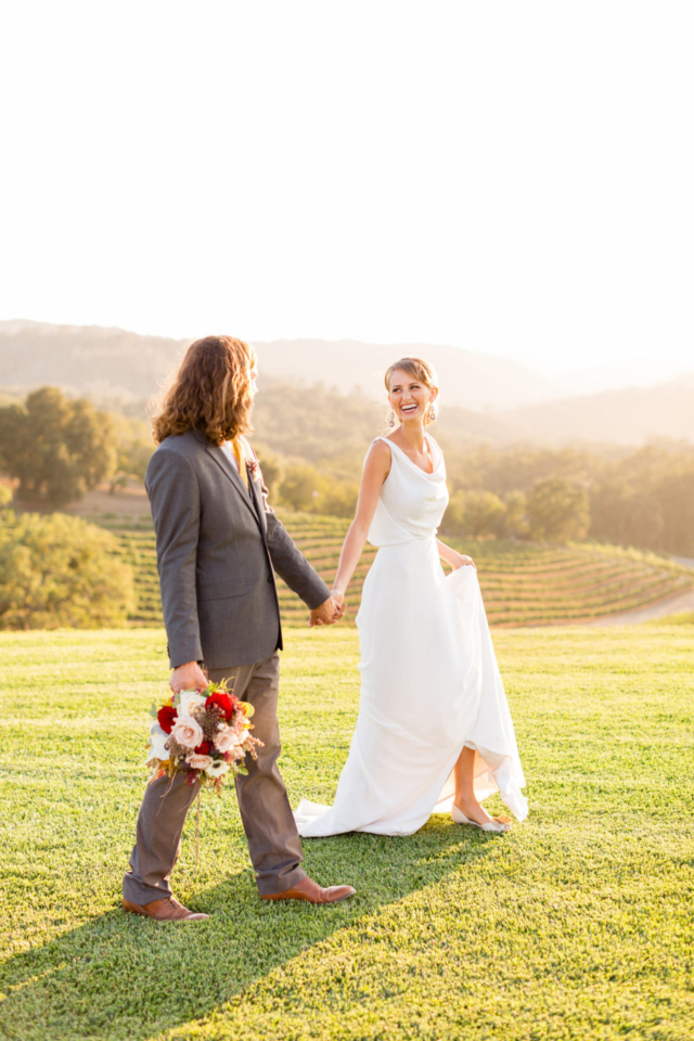 Bride and groom walking together in the vineyards at Opolo Vineyards