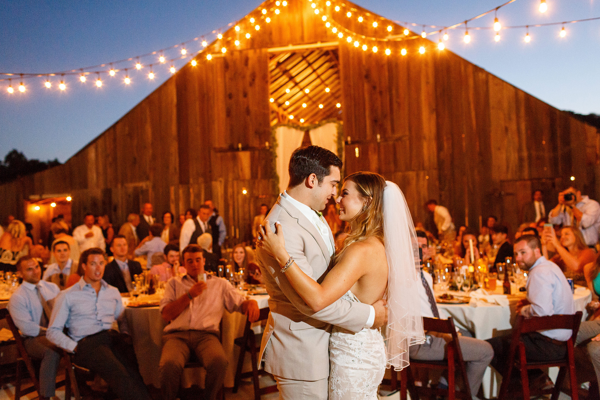 Cute bride and groom share their first dance under the barn lights at Higuera Ranch in San Luis Obispo, CA